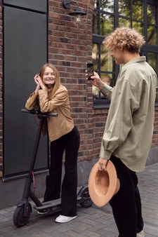 Man taking picture of his girlfriend with electric scooter