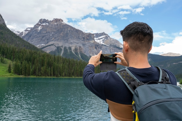 A man taking a picture to the mountains