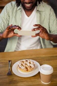 Человек фотографируя торт один