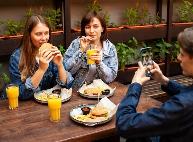 ハンバーガーを食べる女性の友人の写真を撮る男