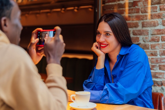 カフェで友達の写真を撮る男