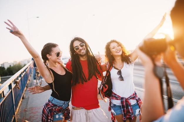 橋の上で楽しい時間を過ごしている3人の友人の写真を撮る男。
