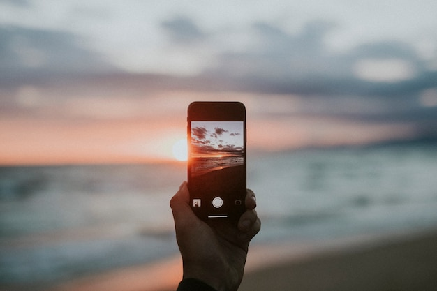 Man taking a picture of the sunset on the beach
