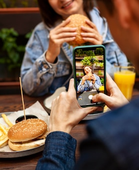 Man taking picture of woman eating burger