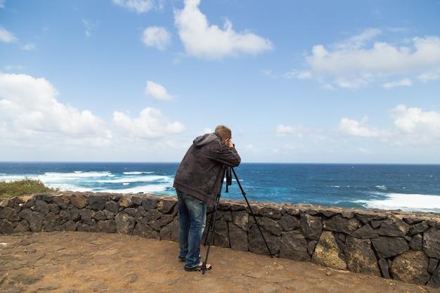 海の風景の写真とビデオを撮る男。