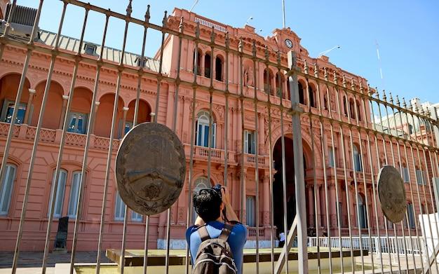 Мужчина фотографирует casa rosada (розовый дом), буэнос-айрес, аргентина