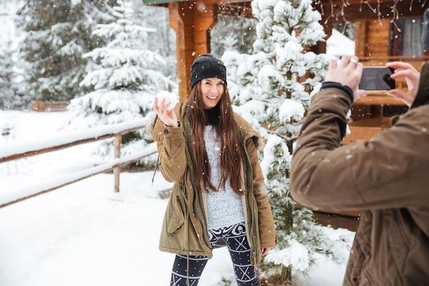 冬の雪の降る天気で雪玉と彼の笑顔のかわいいガールフレンドの写真を撮る男