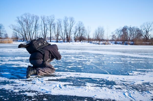 강과 얼음으로 덮여 사진을 찍는 남자