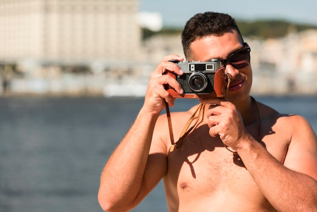 Man taking pictures with camera on the beach