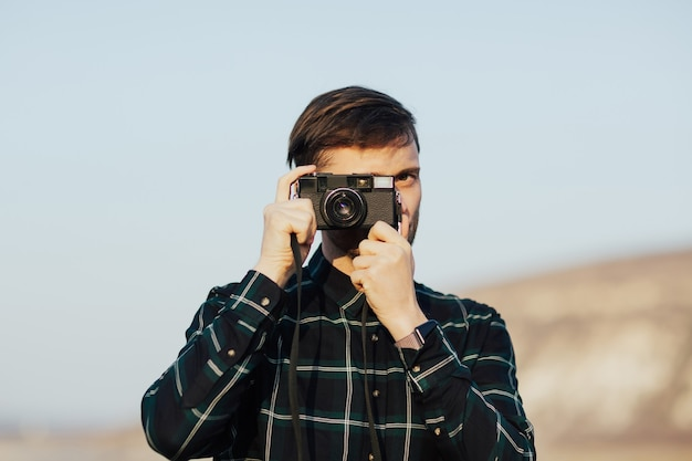 Man taking pictures with retro photo camera looking at camera