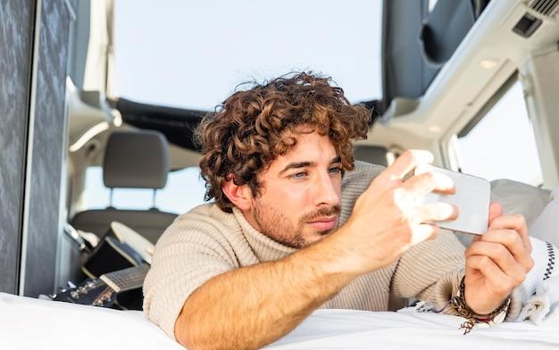 Uomo che scatta foto con lo smartphone dall'auto durante un viaggio