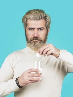 頭痛に対してピルを服用している男性。コップ一杯の水でピルを服用している男性。男はいくつかの錠剤を取り、水のガラスを保持し、青で隔離。