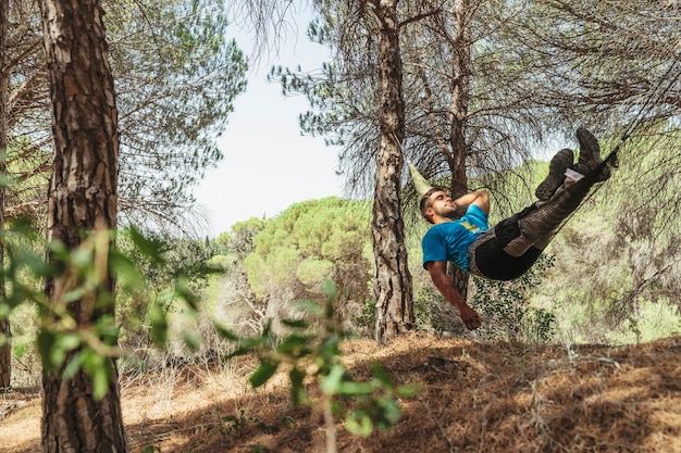 Man taking a rest in hammock in forest