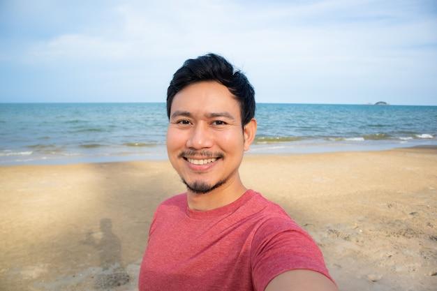 Man taking selfie on the beach.