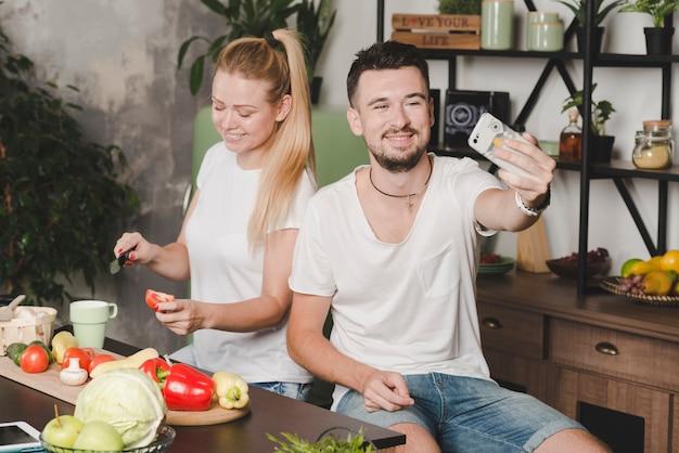 Man taking selfie of her girlfriend cutting tomato slice