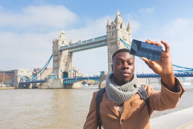 Man taking selfie in london with tower bridge