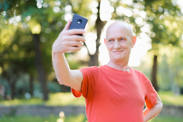 공원에서 휴대 전화에 selfie를 복용하는 사람. 고품질 사진