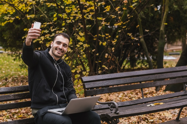 Man taking a selfie and smiling while working in the park