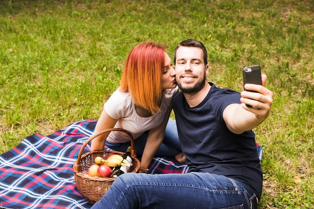Man taking selfie through mobile phone with her girlfriend kissing him on cheek at picnic