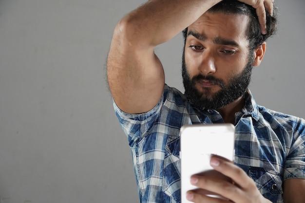 Человек, делающий селфи с помощью мобильного телефона в зеркале