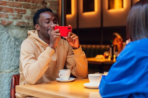 カフェに座って女性と一緒に自分撮りをしている男性。