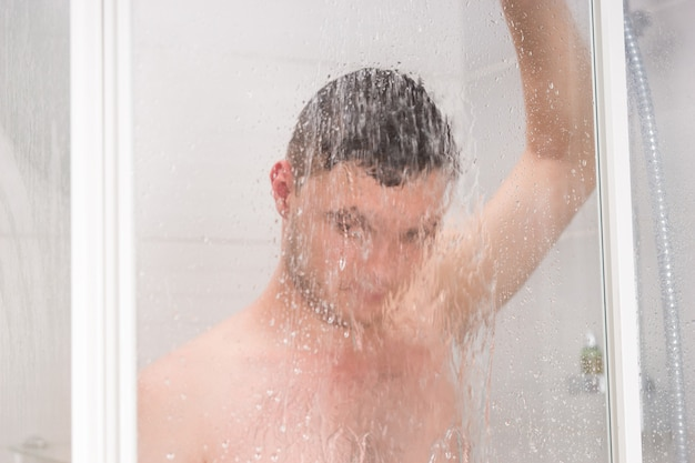 Man taking a shower and holding shower head while standing under flowing water behind transparent misted glass door in the bathroom