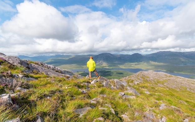 Человек делает снимок в горах коннемара, наслаждаясь видом.
