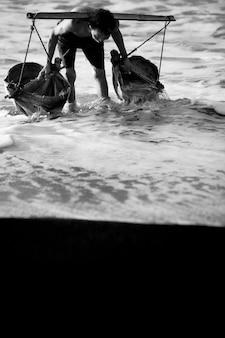 Человек принимает воду из моря