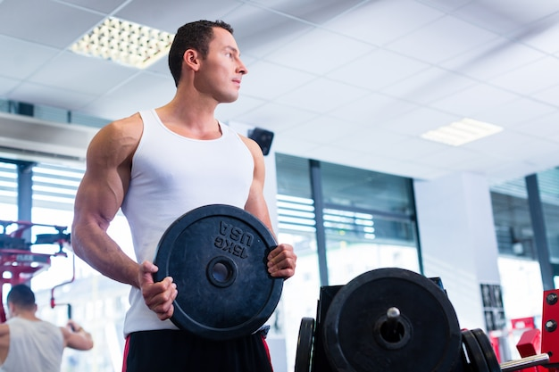 Man taking weights from stand in fitness gym