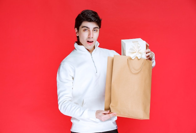 Man taking a white gift box out of a cardboard shopping bag.