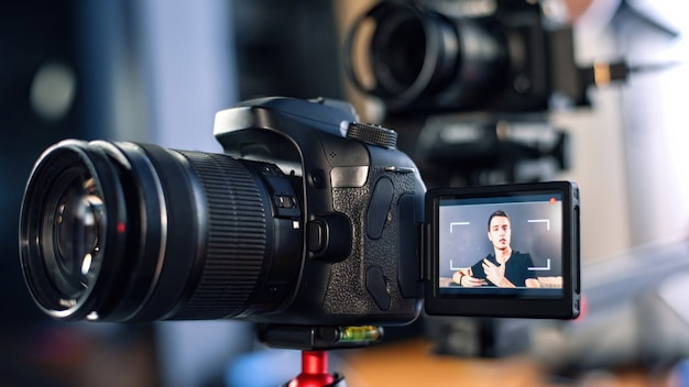 남자가 카메라를 향해 이야기하고 동영상 블로그에 자신을 기록합니다. 재택 근무. 젊은 콘텐츠 제작자. 여러 대의 카메라