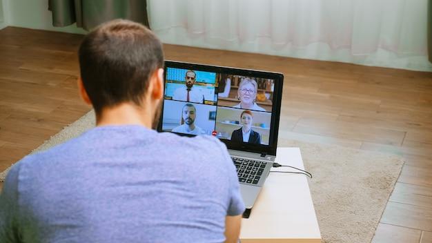 世界的大流行の時代のウェビナー中にビデオ通話でビジネス戦略を話している男性。