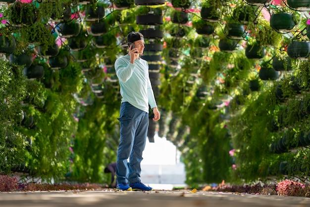 Мужчина разговаривает по мобильному телефону в красочной цветочной арке с зонтиками на вокзале корниш. доха, катар.