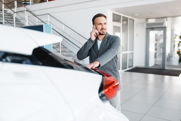 Man talking by phone near the new car in showroom