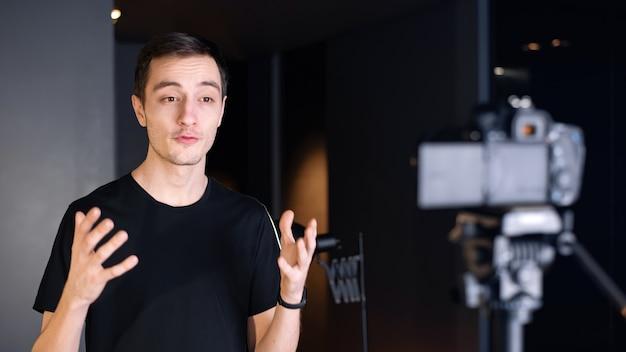 Uomo che parla alla telecamera, registrandosi in un vlog. lavorare da casa. giovane creatore di contenuti