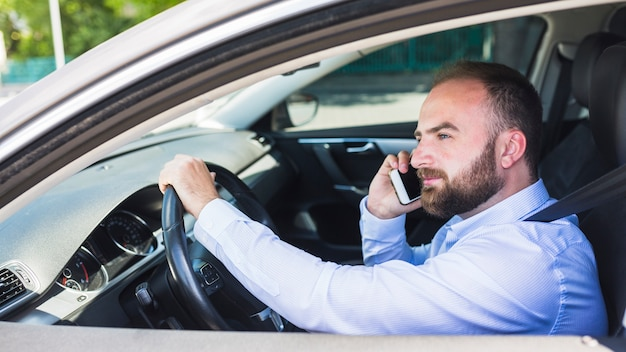 Man talking on cellphone while driving car