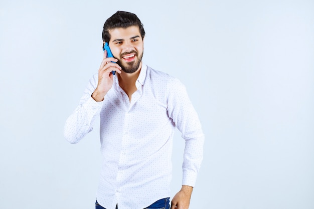 Man talking to his blue new model smartphone