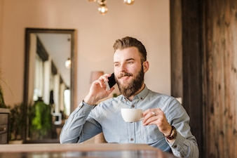 Man talking in mobile phone while drinking coffee