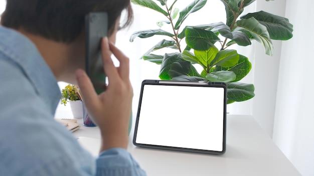 モックアップ、テンプレートの作業テーブルの背景に黒い画面でデジタルタブレットを見ながらモバイルphineを話している男