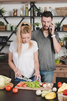 Man talking on mobile phone looking at wife cutting vegetables with knife in the kitchen