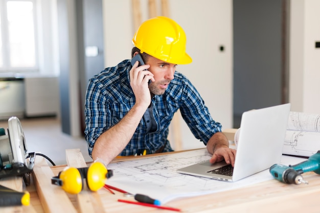 Man talking on mobile phone and using laptop on construction side