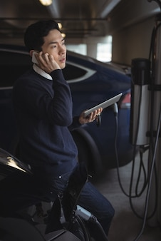 Man talking on mobile phone while charging electric car