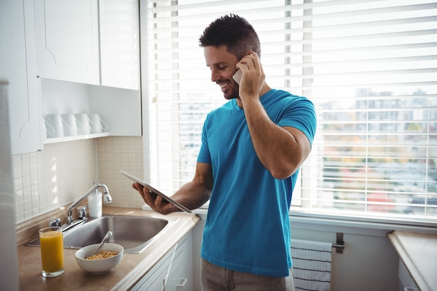 Man talking on mobile phone while using digital tablet in kitchen