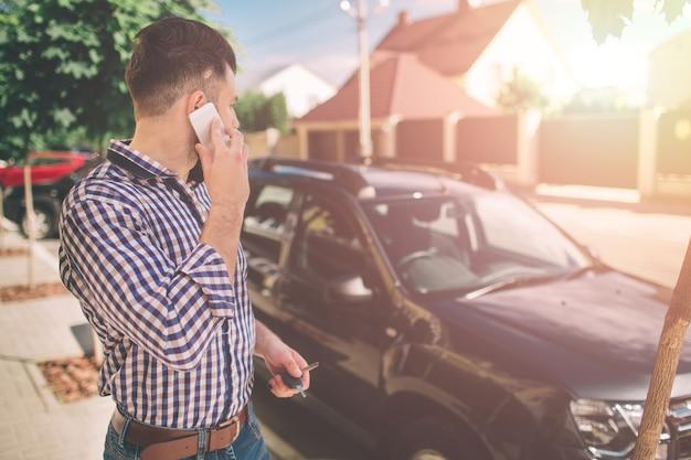 휴대 전화로 이야기하고 그의 차를 보는 남자