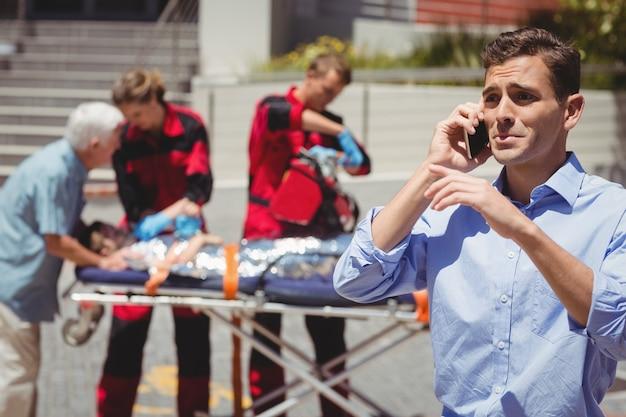 携帯電話で話している男とバックグラウンドで負傷した少年を調べる救急隊員