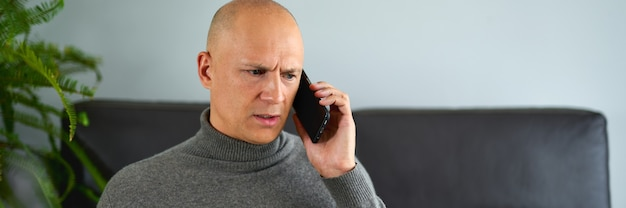 Человек разговаривает по мобильному телефону на диване