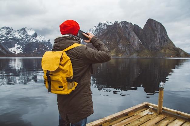 산과 호수 배경에 서 있는 노란색 배낭을 메고 휴대전화로 통화하는 남자