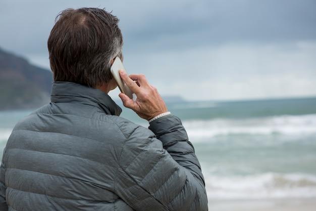 Человек разговаривает по мобильному телефону на пляже