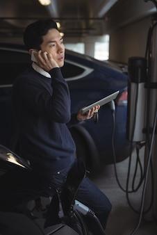 電気自動車を充電しながら携帯電話で話している男