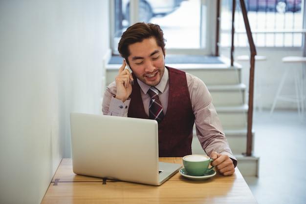 コーヒーを飲みながら携帯電話で話している人